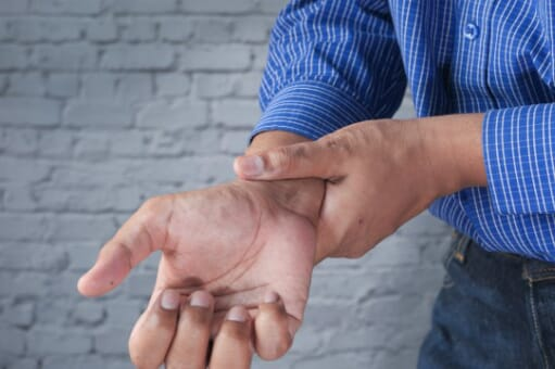 man in office holding his arthritic wrist